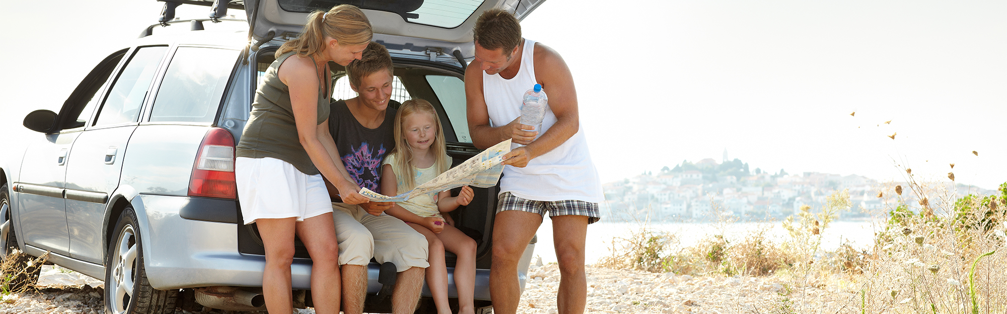 Family looking at map by the car.